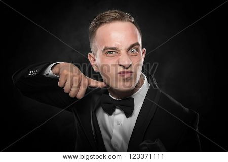 Businessman in suit gesturing a cutting motion on her throat over dark background.