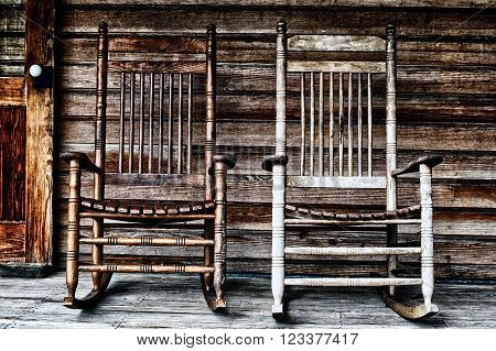 Two old wooden rocking chairs on front porch part of door and the house's wooden shingles can be seen.