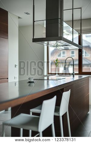 Brown kitchen island with cooktop, sink and modern range hood over it on the brown window background. Walls are light. There is a white cup with saucer on the tabletop. Two white chairs are near the kitchen island. On the floor there are gray tiles.