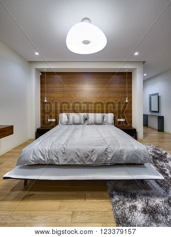 Bedroom in a modern style with light walls. There is a big bed with gray bedcover and pillows. On the both sides of the bed there are dark wooden bedside tables. On the back wall there is a big niche with wooden panel, hanging lamps and switches with powe