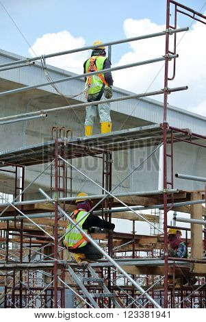 SELANGOR, MALAYSIA -FEBRUARY 23, 2016: Construction workers wearing safety harness and working at high level at the construction site in Selangor, Malaysia.