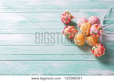 Cake pops on turquoise painted wooden background. Selective focus.Place for text.