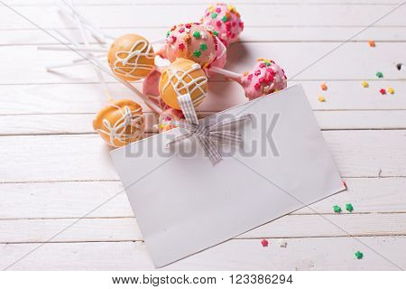 Cake pops and empty tag on white wooden background. Selective focus.Place for text.