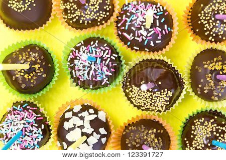Cake pops with chocolate over yellow background
