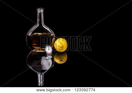 Bottle of Brandy and lemon with watch on black background