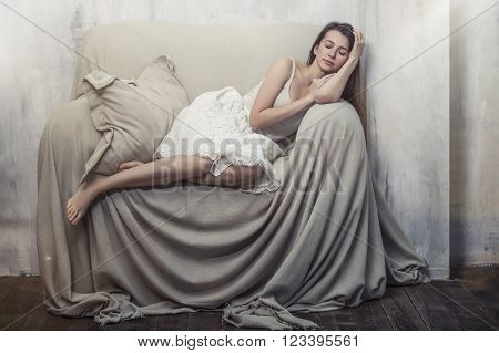 Beautiful young slim woman sleeping in a huge comfortable chair in white