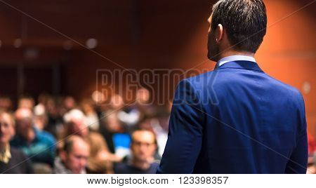Speaker giving a talk on corporate Business Conference. Audience at the conference hall. Business and Entrepreneurship event. ** Note: Soft Focus at 100%, best at smaller sizes
