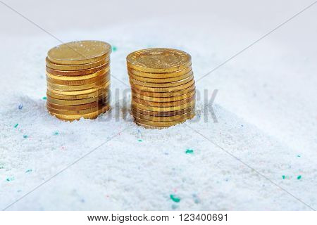 Saving money on quality cost-effective washing powder stacked coins in laundry detergent.