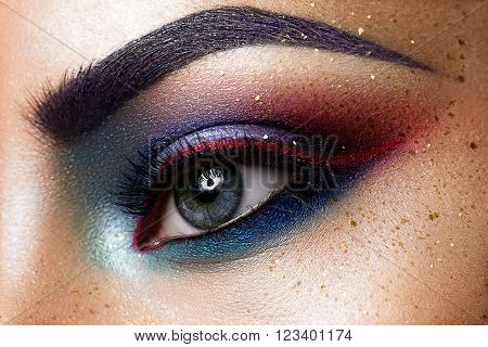 Close-up of beautiful womanish eye. Colored eyeshadows