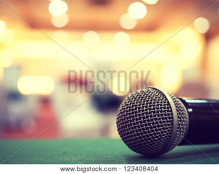 Silver microphone on the table in concert hall or conference room with defocused bokeh lights in background. Extremely shallow dof. : Vintage style and filtered process.