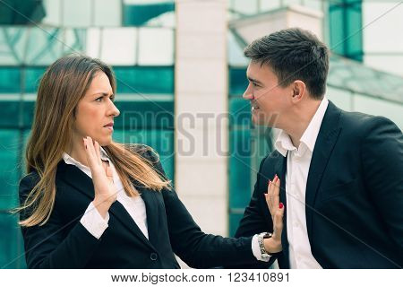 Workplace harassment - young business woman stopping aggressive colleague