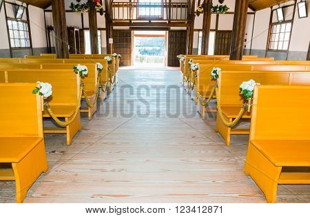 church interior with empty a row of wooden pews.