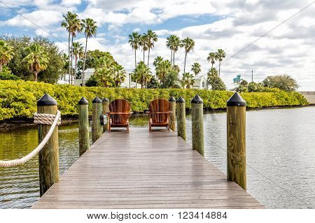 Adirondack chairs on a wooden pier in the tropics