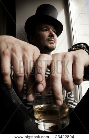 Danger man in top hat with glass of whiskey sitting on windowsills