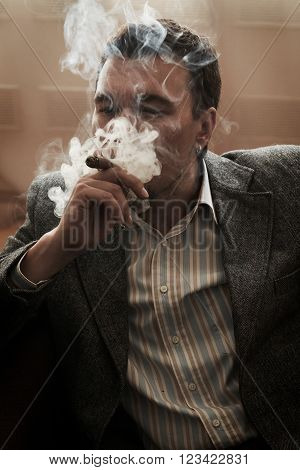 A man smokes a cigar in the room