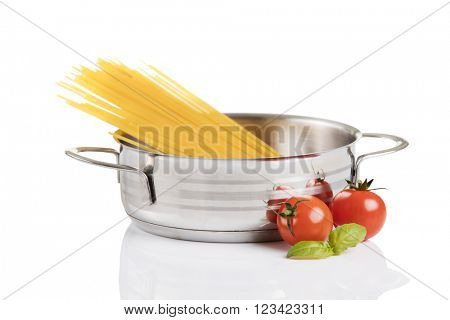 Raw pasta in metallic pot isolated on white background