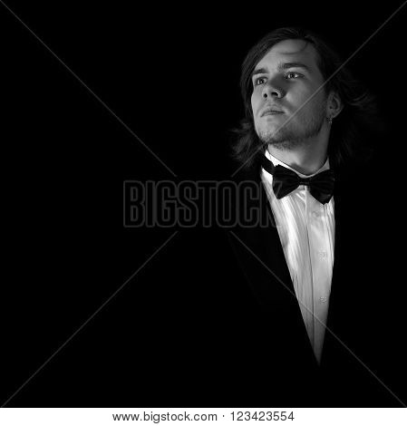 Confident musician over black background in black