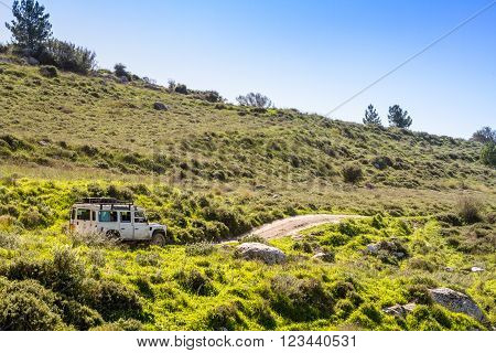 SUV rides on the country road among hills and meadows in Neve Shalom Israel