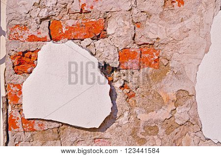 Textured architectural background - aged weathered wall made of red brick.