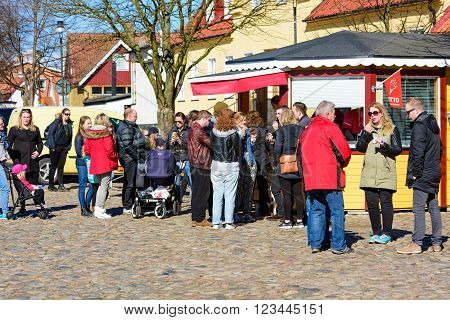 Ahus Sweden - March 20 2016: Lots of ice cream craving people stand in line to buy a cone from the Otto Glassfabriken ice cream stand in the city square. Real people in everyday life.