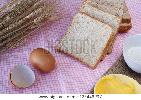 Stiil life with whole wheat bread,egg,magarine,flour and wheat on table