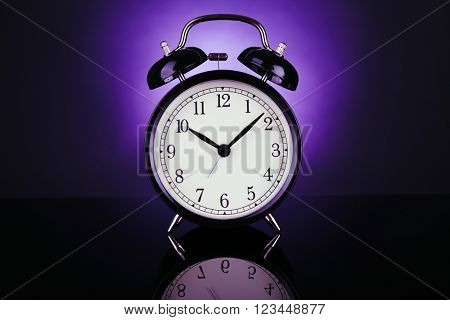 Alarm clock on a dark purple background.