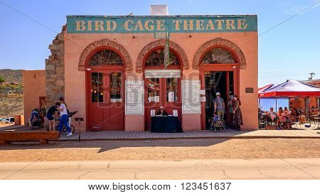 TOMBSTONE, ARIZONA - MARCH 20: A stagecoach loaded with tourists passes the historic Bird Cage Theatre in Tombstone, Arizona on March 20th, 2016.