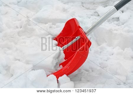 Winter concept. Red shovel for snow removal