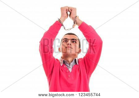 man in handcuffs looking at his hands with regret and remorse