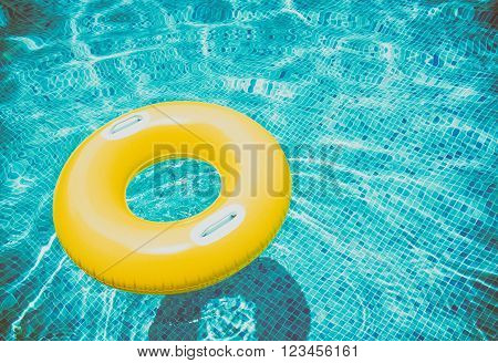 rubber ring floating in transparent blue pool, retro toned