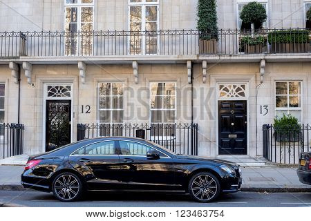 LONDON UK - April 14: Houses in London english architecture. Luxury black Mercedes Executive car parked near the house.