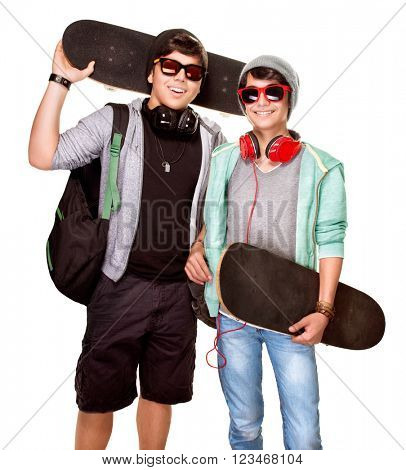Portrait of two happy stylish skateboarders isolated on white background, best friends enjoying sport, active sportive teens