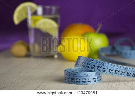 blue measure tape and products (fresh vegetarian fruits and healthy drink) for diet and weight loss program