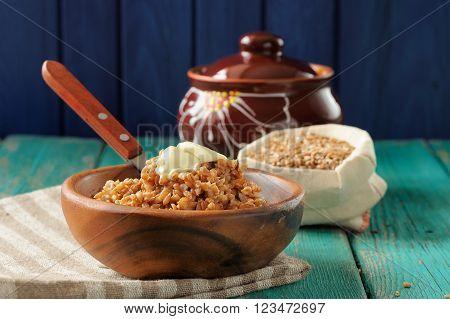 Spelt porridge buttered in wooden bowl and raw spelt in linen bag on wooden table closeup