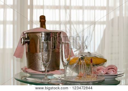 Champagne bottle in ice bucket with fruit bowl and Hors d'oeuvres