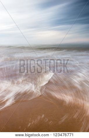 A blurred motion seascape featuring ocean waves and a dramatic overcast sky.