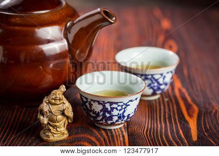 Broun ceramic teapot and cups for the tea ceremony on rustic wooden table