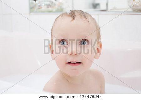 photo of little boy washing in bath