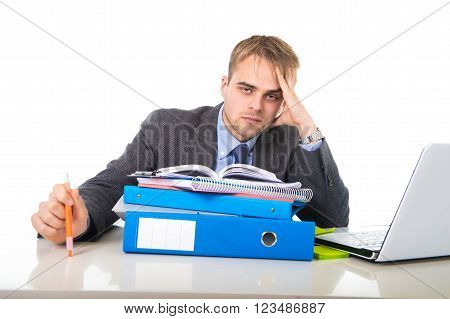 young businessman overworked and overwhelmed suffering work stress at office computer desk looking tired sad and frustrated