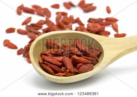Dried Goji berries in wooden spoon on white isolated background