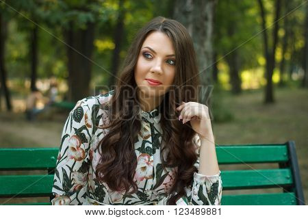 Beautiful brunette girl poses on bench in park outdoors
