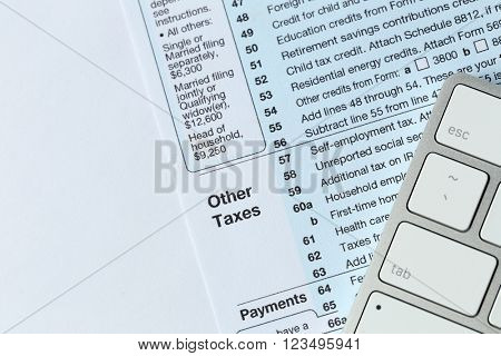 1040 Individual Income Tax Return Form for 2015 year with a computer keyboard on the white desk, top view