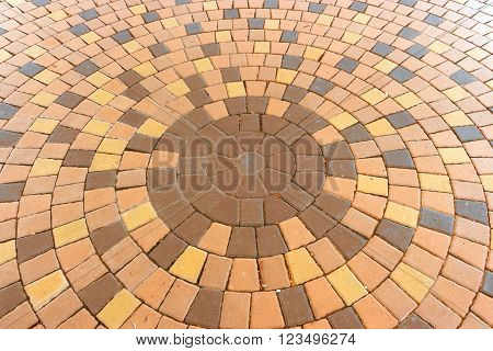 Architectural background of an ornamental pattern in outdoor patio paving with bricks arranged in a circular pattern of concentric geometric circles