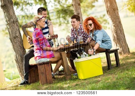 Curly red-haired girl takes out cold beer from picnic handheld refrigerator at summer camp in nature