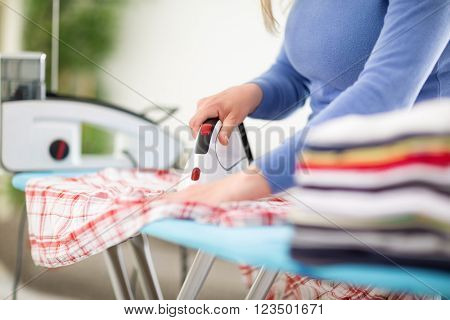 Close up of iron and housekeeper ironing