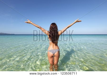 Beautiful young woman in bikini posing in sea