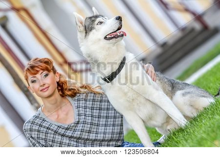 Happy young woman sitting with her dog on grass in park