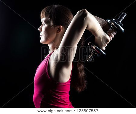 Athlete woman with weights on black background