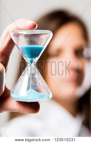 hourglass with a light blue sand flowing held by a woman (blurred) concerned about times that goes by