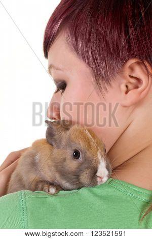 Teenager girl hugging her little rabbit on her shoulder